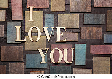 Wooden letters forming words I LOVE YOU written on wooden background