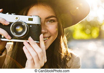 Image of positive woman taking photo on retro camera outdoors