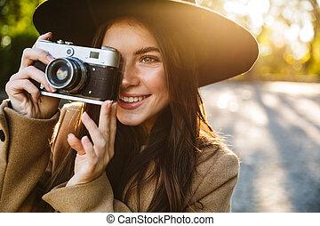 Image of seductive woman taking photo on retro camera outdoors