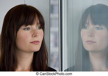 A beautiful young woman stares wistfully into a window where her reflection looks back at her.