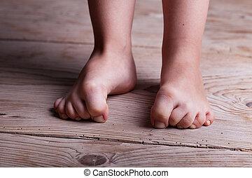 Indecision in childhood - kids feet on old wooden floor