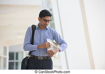 Indian man checking on new office to let, holding newspaper and