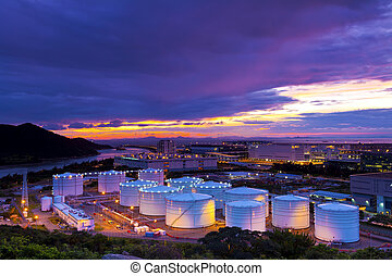 Industrial oil tanks at sunset