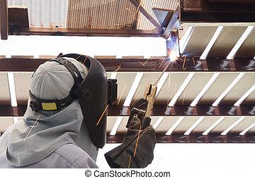 Industrial worker welding steel pipe flange, a spark welding.
