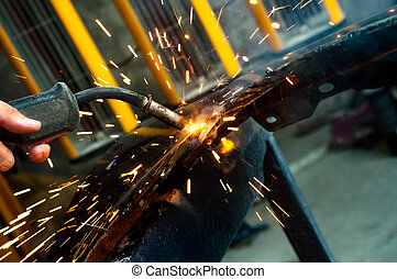 industrial worker welding with sparks