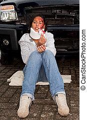 Injured woman sitting next to her crashed car