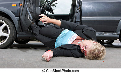 Injured driver with a laceration in her forehead, dropping unconciously out of her car after having had an accident