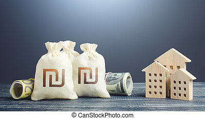 Israeli shekel money bags and residential buildings figures. Financing the construction of new settlements. Municipal budget management. Investments in real estate. Mortgage loan. Taxes.