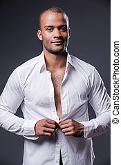 It is my favorite shirt. Handsome young black man dressing up his shirt and smiling while standing against grey background