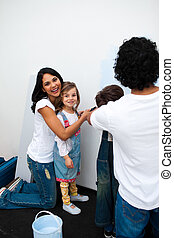 Jolly parents with their children painting a room