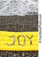 joy message from pebbles on a air-bed. air-bed is laying on a sea coast near water.