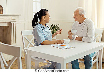 Joyful delighted man listening to his caregiver