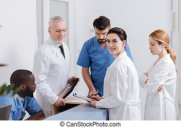 Joyful pediatricians enjoying conversation at the reception area of the clinic