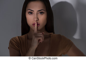 Keep silence. Beautiful young woman holding finger on mouth and looking at camera