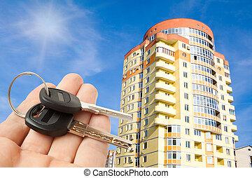keys on hand with house on blue sky
