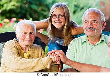 Kind Family Visiting Elderly Lady