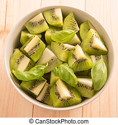 Kiwi fruit sliced segments in a round bowl on a wooden background