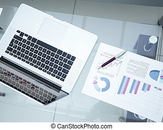 laptop, financial graph and pen in the workplace of a businessman.