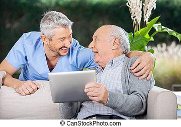 Laughing Caretaker And Senior Man Using Tablet Computer