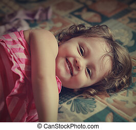 Laughing kid girl lying on the bed. Vintage portrait