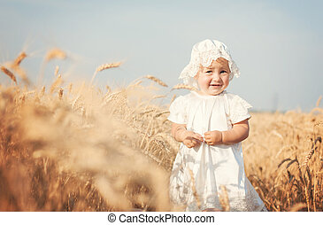 Laughing kid in sunny wheat field