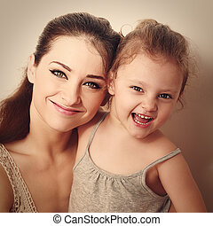 Laughing kid together with happy young mother. Closeup vintage portrait