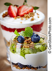 Healthy layered cream desserts with fresh berries and muesli on wooden background