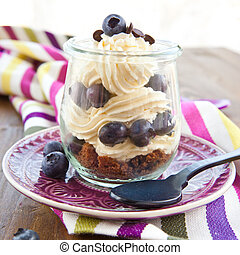 Layered cream dessert in a jar with fresh blueberries