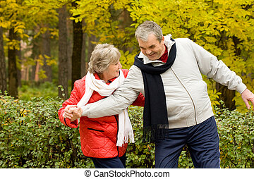 Photo of two aged people having fun during walk in autumn forest