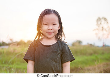 Little asian girl smiling outdoor with sunset