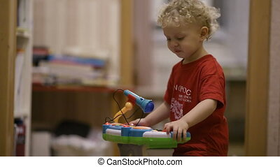 Little boy dancing to music of his musical playing set, tnen sitting down and pushing buttons.