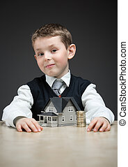 Little boy with home model and pile of coins