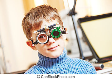 little boy with phoropter at ophthalmology clinic