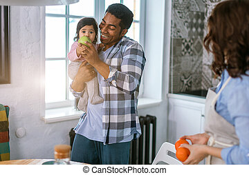 little girl eathing fruit while being hold in her daddy's arms