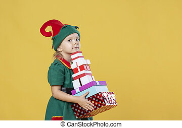 Little girl in a Christmas elf costume on a yellow background. A child is holding a pile of presents.