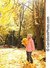 little girl walks in the autumn park