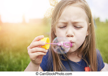 Little girl with big soap bubble