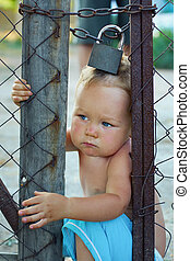 locked baby boy trying to escape through wire fencing with padlock. outdoors