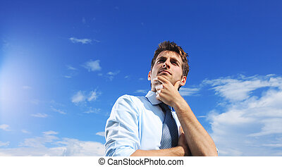 Young business man looking up against a blue sky
