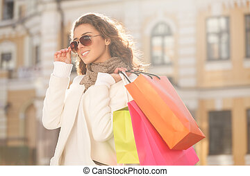 Looks great with her new sunglasses. Beautiful young women in sunglasses holding the shopping bags and looking away