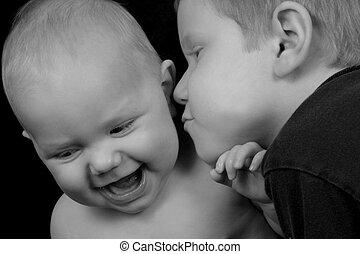 Boy kissing his baby sister