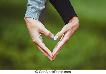 Man and woman holding by hands and making love heart