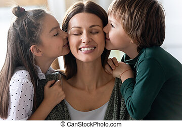 Loving little kids siblings kissing cheeks of affectionate young mommy.