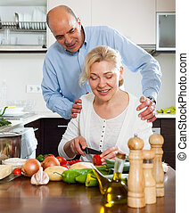 Loving mature woman with husband cooking