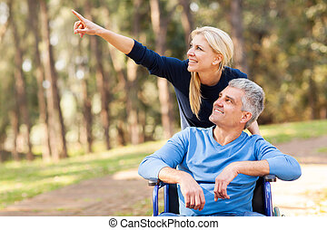 loving mid age wife taking injured husband for a walk