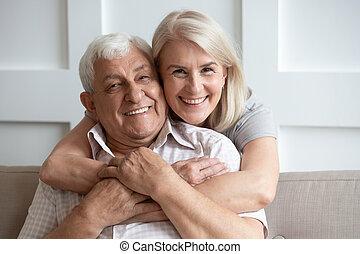 Loving senior husband and wife hugging looking at camera