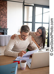 Loving wife coming to husband filling tax declarations