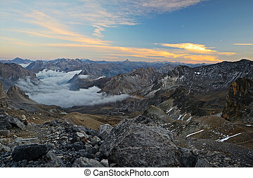 View from a high mountain trail taken at 3000 m just after sunset during the descend from Mount Thabor, italian-french Alps.