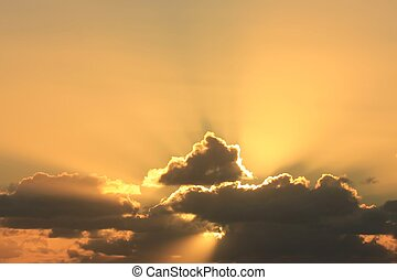 Beams of golden light flow out from the clouds.