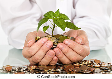 Businessman holding plant sprouting from a handful of coins - good investment and money concept